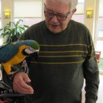 Ein Pflegeheim-Bewohner trägt einen Papageien auf dem Arm.